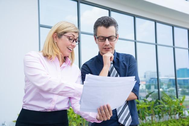 Content partner commerciali discutendo documenti al di fuori dell'ufficio. Foto Gratuite