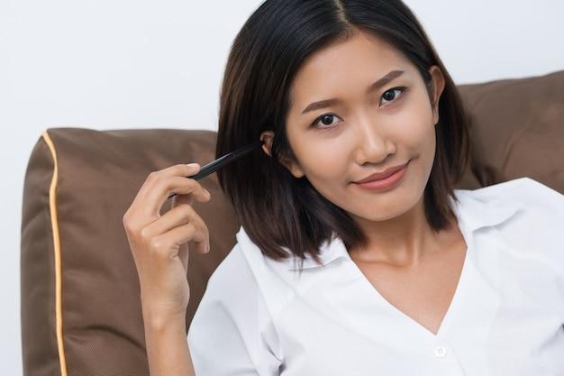 Contenuto pretty woman asiatica che si appoggia sul cuscino Foto Gratuite