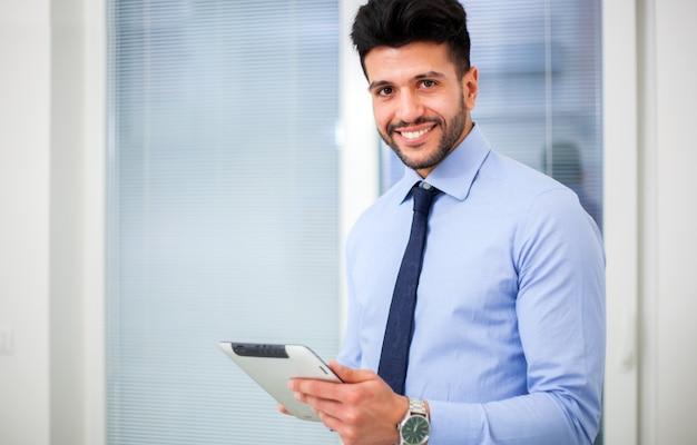 Controllando la sua posta giovane uomo d'affari bello che utilizza il suo touchpad mentre stando nell'ufficio. Foto Premium