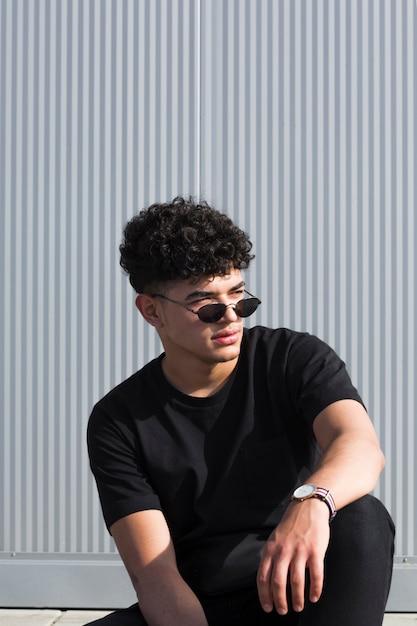 Cool ragazzo nero con i capelli ricci in occhiali da sole Foto Gratuite