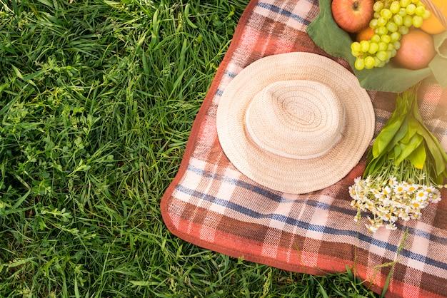 Coperta da picnic con frutta e cappello Foto Gratuite