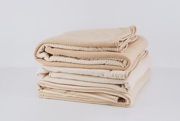 Coperta di cotone beige naturale piegata avvolta mucchio del primo piano su bianco Foto Premium