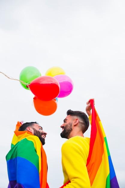 Copertura maschio allegra delle coppie nella bandiera dell'arcobaleno sulla parata di gay pride Foto Gratuite
