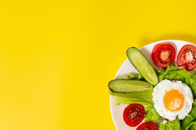 Copi lo spazio uovo fritto con il piatto degli ortaggi freschi su fondo normale Foto Gratuite