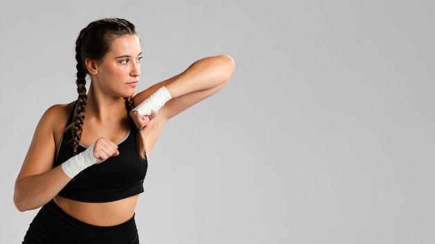 Copia spazio e adatta la donna in posizione di combattimento Foto Gratuite