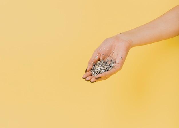 Copia spazio sfondo arancione con mano e glitter Foto Gratuite
