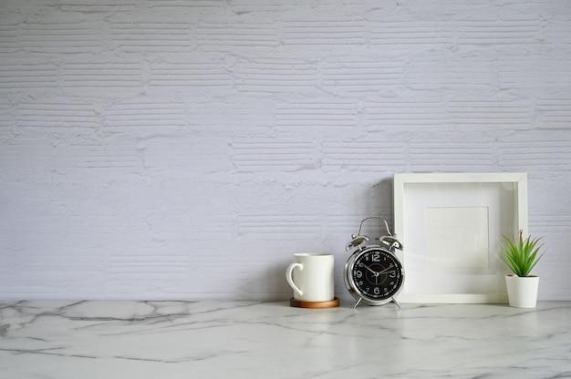 Copia spazio sveglia. caffè, cornice per foto e decorazione vegetale sul tavolo di marmo bianco e muro di mattoni. Foto Premium