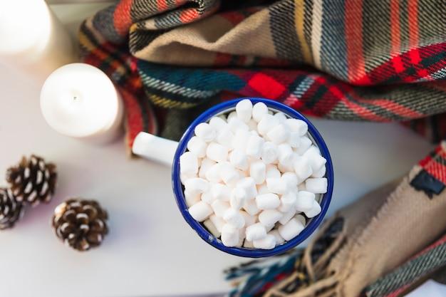 Coppa con marshmallow vicino a candele e sciarpa Foto Gratuite