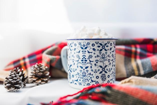 Coppa con marshmallow vicino sciarpa Foto Gratuite
