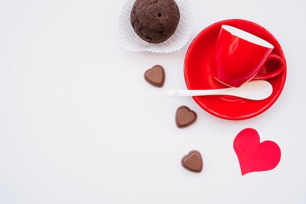 Coppa sul piatto vicino al cioccolato dolce caramelle, muffin e cartolina di san valentino Foto Gratuite