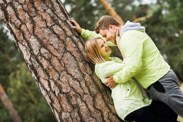 Coppia abbracciare accanto a un albero Foto Gratuite