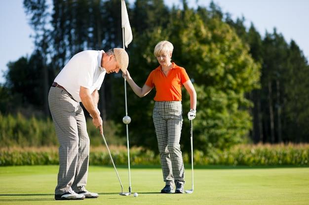 Coppia adulta giocando a golf Foto Premium