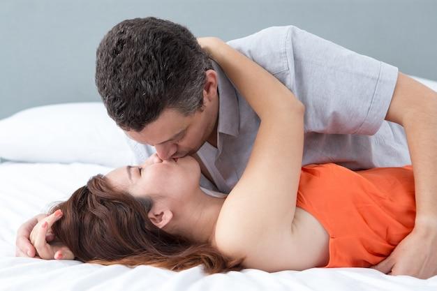 Coppia appassionata che abbraccia e bacia nel letto   Scaricare ...
