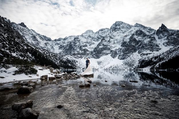 Coppia appena sposata che bacia sul paesaggio delle montagne Foto Premium