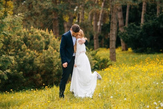 Coppia appena sposata che si diverte all'aperto nel parco, bella sposa e lo sposo. la sposa ha sollevato una gamba dalla felicità. Foto Premium