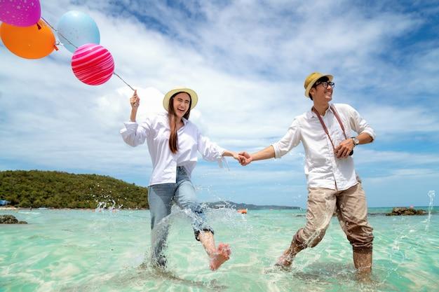 Coppia asiatica in esecuzione e felice sulla spiaggia di pattaya con palloncino a portata di mano Foto Premium