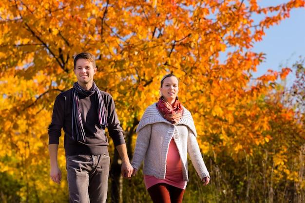 Coppia avere camminata davanti agli alberi variopinti in autunno Foto Premium