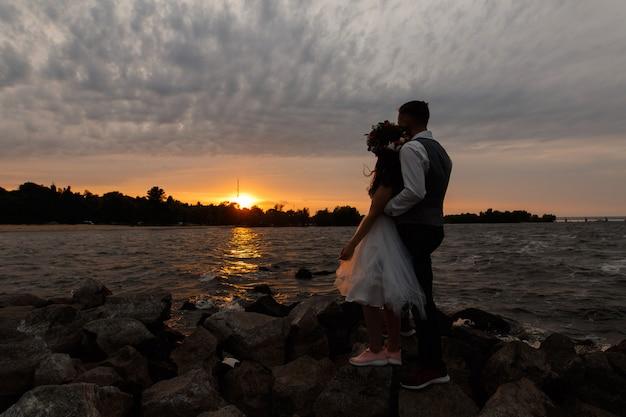 Coppia bel matrimonio sulla spiaggia rocciosa. sposi alla moda in scarpe da ginnastica per mano e abbracci all'aperto al tramonto. sposi in piedi sulla riva del mare. giorno del matrimonio sulla natura. appuntamento romantico Foto Premium