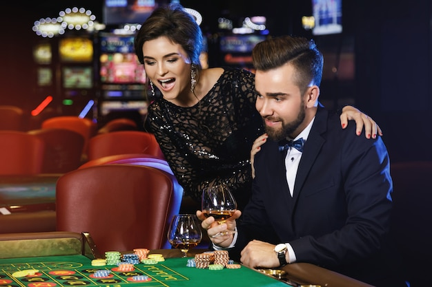 Coppia bella e ricca che gioca alla roulette nel casinò Foto Premium