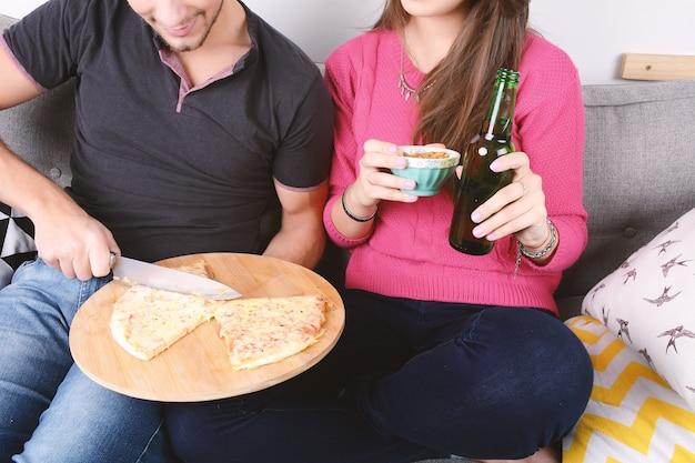 Coppia bere birra e mangiare la pizza. Foto Premium