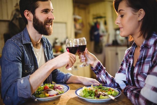 Coppia brindando con bicchieri di vino Foto Gratuite