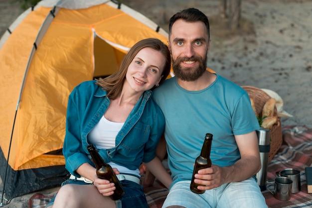 Coppia campeggio felice guardando la fotocamera Foto Gratuite