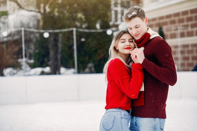 Coppia carina e amorevole maglioni rossi in una città d'inverno Foto Gratuite