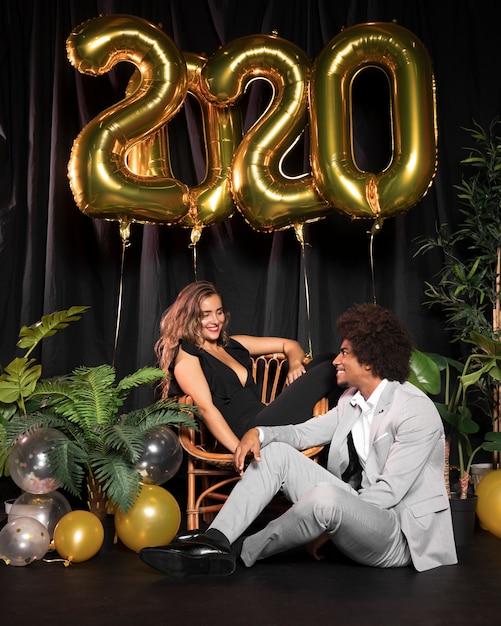 Coppia carina guardando l'altro circondato da palloncini con 2020 nuovo anno Foto Gratuite