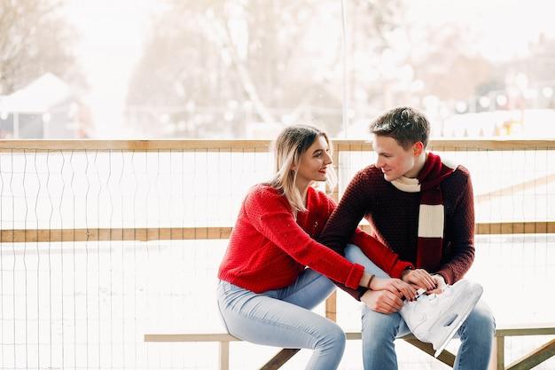 Coppia carina in maglioni rossi si aiutano a pattinare Foto Gratuite