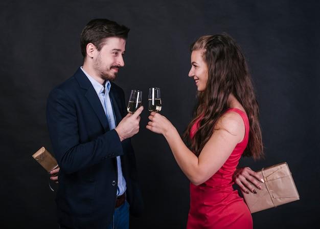 Coppia con bicchieri di champagne, nascondendo regali alle spalle Foto Gratuite
