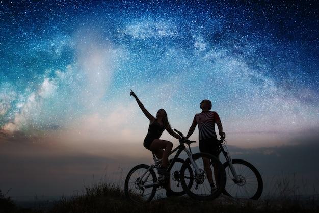 Coppia con mountain bike sotto il cielo stellato di notte Foto Premium