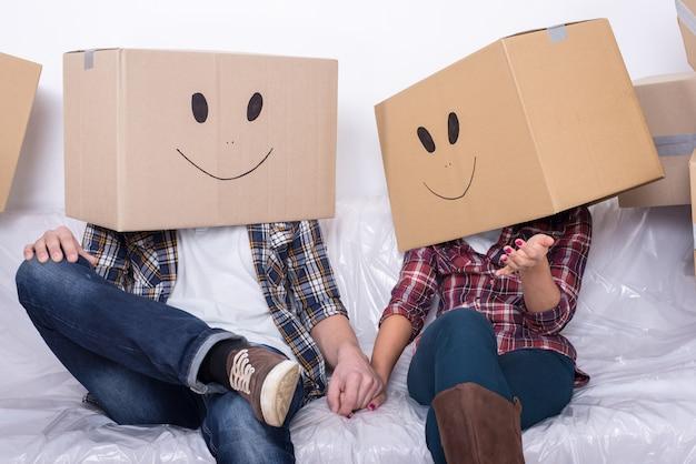 Coppia con scatole di cartone in testa con faccina sorridente Foto Premium