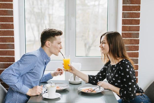 Coppia con un succo d'arancia in un ristorante Foto Gratuite