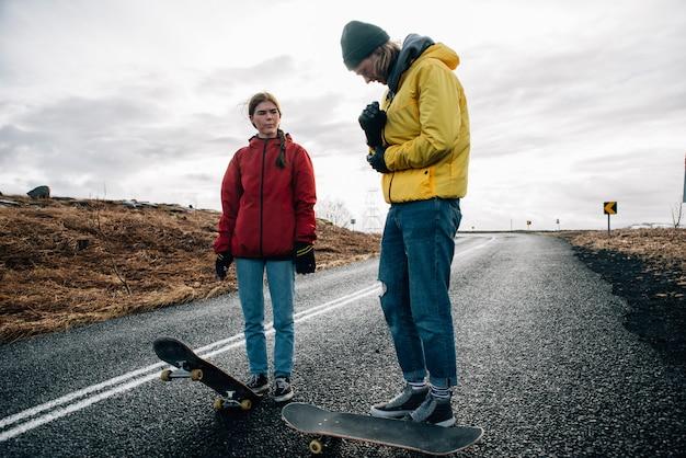 Coppia di adolescenti che si divertono pattinando e facendo discesa Foto Premium