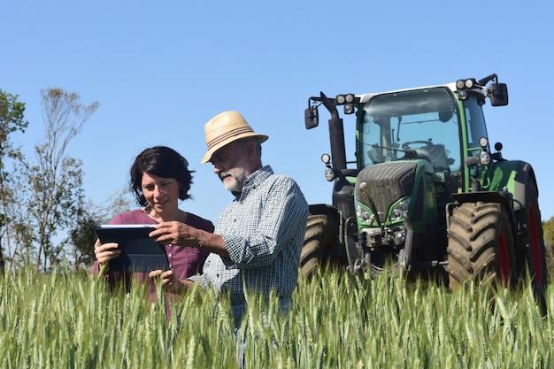 Coppia di agricoltori in un campo con una tavoletta digitale Foto Premium