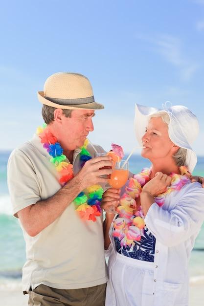4be36eeefbd9 Coppia di anziani bevendo un cocktail sulla spiaggia | Scaricare ...