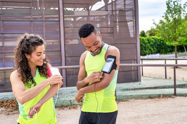 Coppia di atleti che collegano le cuffie allo smartphone che portano tra le braccia Foto Premium