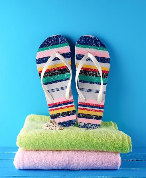 Coppia di ciabatte da spiaggia e asciugamani Foto Premium