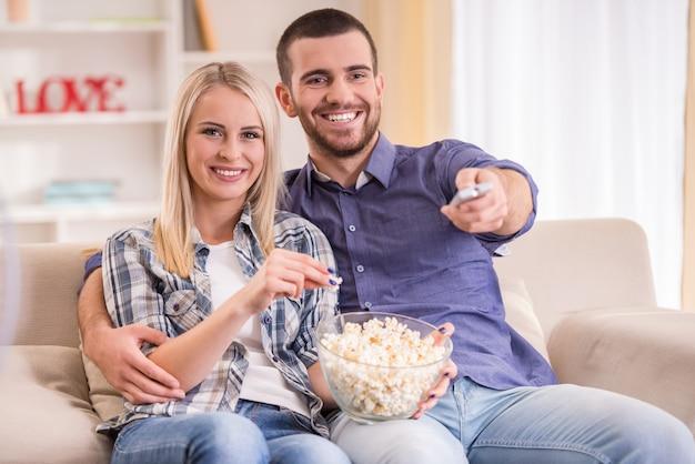 Coppia di giovani innamorati a casa seduto sul divano. Foto Premium