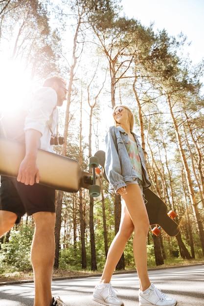 Coppia di innamorati camminando con skateboard all'aperto. guardando da parte. Foto Gratuite