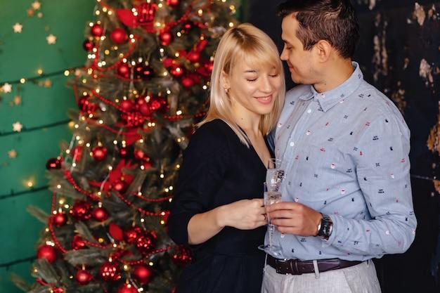 Coppia di innamorati con bicchieri di champagne sullo sfondo di un albero di natale Foto Premium