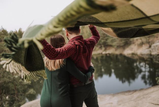 Coppia di innamorati con un tappeto che si sviluppa nel vento sulla riva di un lago con una ripida scogliera Foto Gratuite
