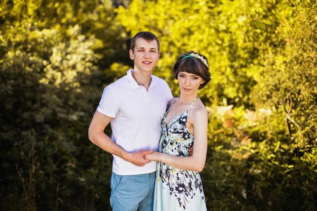 Coppia di innamorati nella foresta di betulle. uomo e donna che camminano sulla natura. si abbracciano. siate felici. stile di vita attivo. foresta d'estate. calda luce del tramonto. Foto Premium