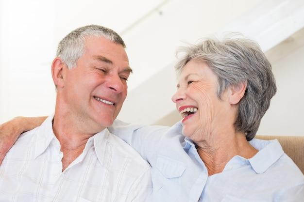 Coppia di pensionati seduti sul divano sorridendo a vicenda Foto Premium
