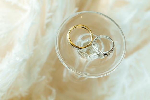 Coppia di sposi anelli di diamanti posizionati con bicchiere di vino e tessuto. Foto Premium