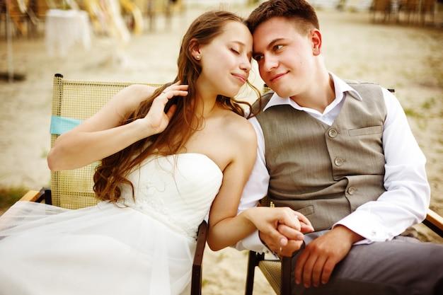 Coppia di sposi seduti vicino all'acqua sulla spiaggia Foto Premium