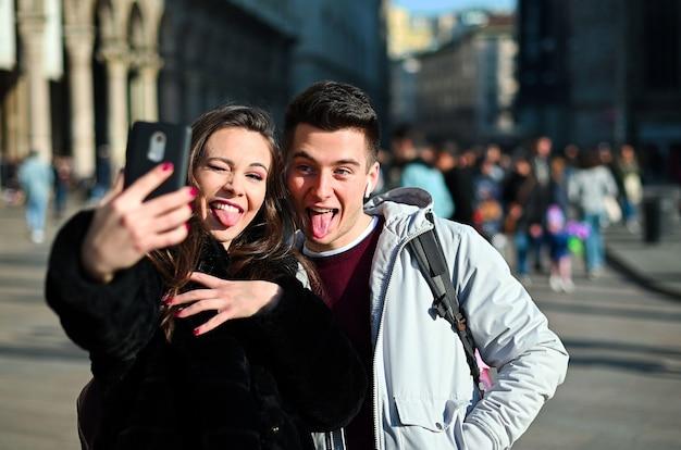 Coppia di turisti che fanno selfie divertenti a milano Foto Premium