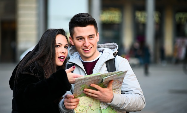 Coppia di turisti in città guardando una mappa e discutendo della prossima destinazione Foto Premium