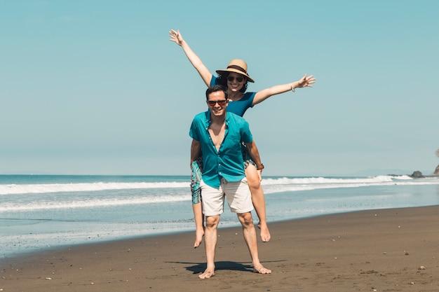 Coppia divertirsi sulla spiaggia Foto Gratuite