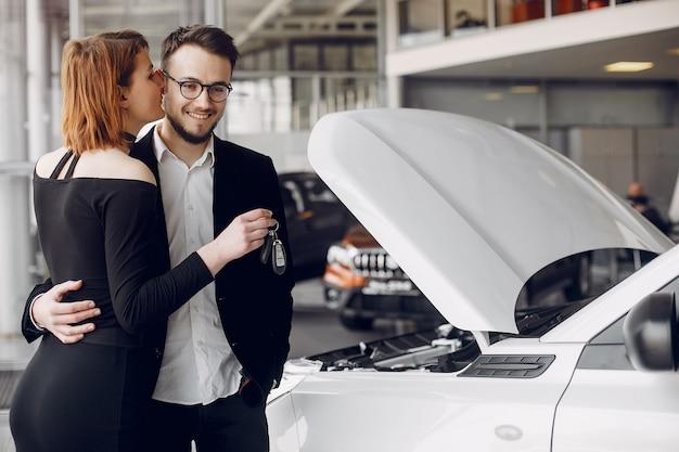 Coppia elegante ed elegante in un salone di auto Foto Gratuite